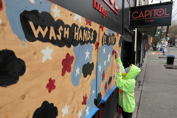 """A woman works on a mural that reads """"wash hands, be kind""""in Seattle amid the coronavirus pandemic. Hundreds of miles aw"""