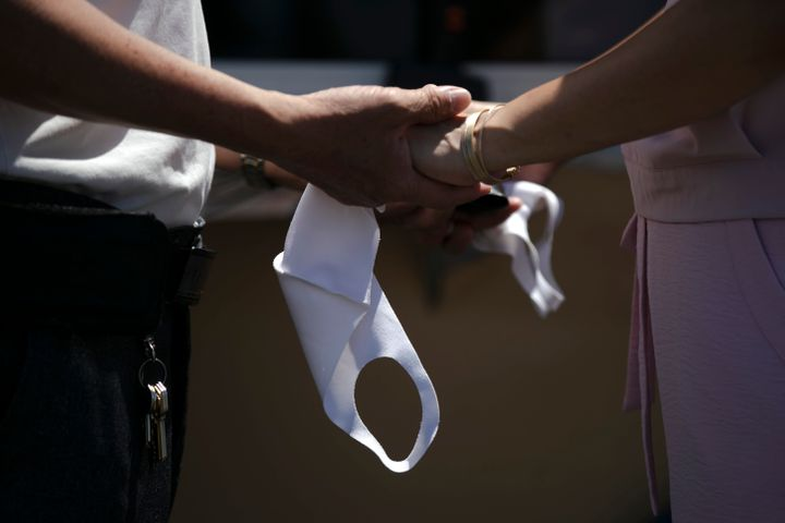 A couple holds hands and masks while exchanging vows during their wedding ceremony in a parking lot in Anaheim, Calif. Couple