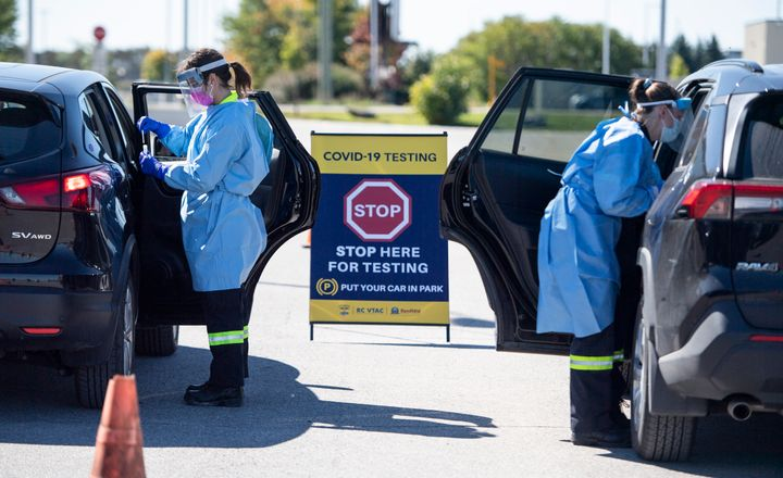 Paramedics administer nasal swabs at a drive through, pop-up COVID-19 test centre outside the Canadian Tire Centre, home of the NHL's Ottawa Senators, in Ottawa on Sept. 20, 2020.