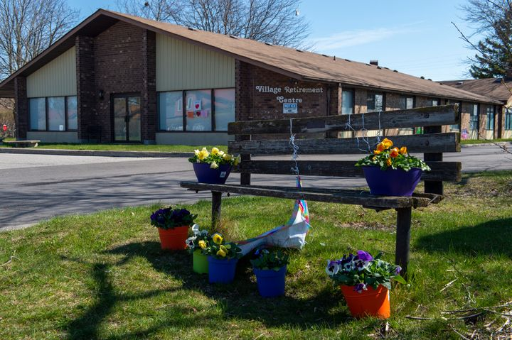 Flowers sit on a bench in front of Orchard Villa care home in Pickering, Ont. on April 27, 2020. Outbreaks of COVID-19 in long-term-care homes have hit residents, health workers, and their families hardest.