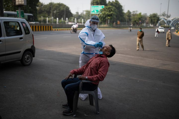 A health worker takes a nasal swab sample of a man to test for Covid-19 during random testing of people at Delhi-Noida border on November 18, 2020.