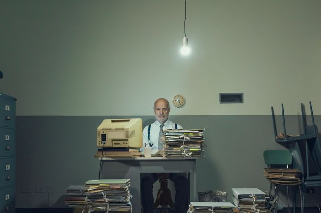 Frustrated vintage style businessman working in a rundown office, he is overloaded with