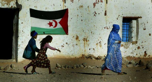 Una mujer y unos niños saharauis pasan ante una bandera, en un campo de refugiados de Samra, Argelia,...