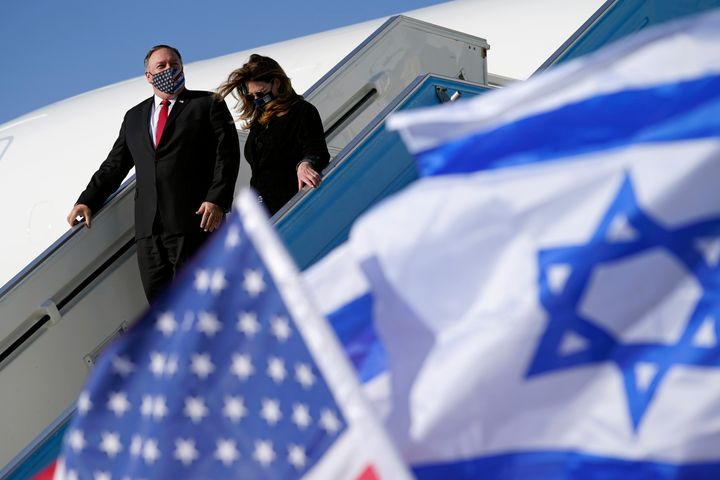 The secretary of state and his wife Susan are seen walking past American and Israeli flags as they step off a plane at Ben Gu
