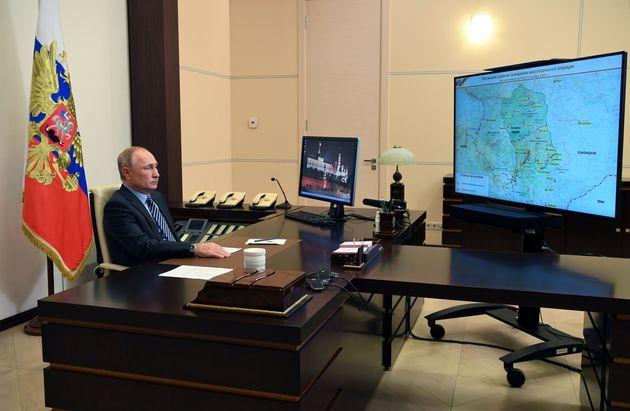 ナゴルノ・カラバフ地域と見られる地図が写し出されたテレビと、ロシアのプーチン大統領