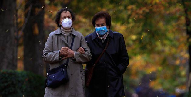 Dos mujeres pasean con sus mascarillas por el parque de El Retiro