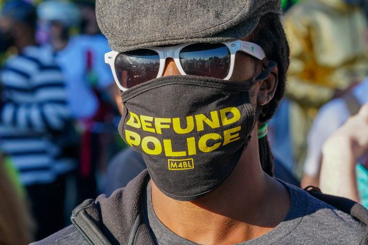"A protester in New York City wears a face mask calling to ""Defund Police."" The activist cry is now the subject of fierce deba"