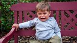 Upset child sitting on bench crying with greenery in the background.