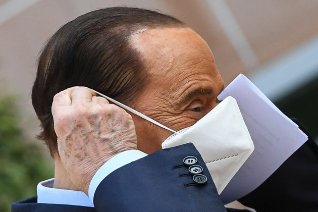 Former Italian prime minister Silvio Berlusconi takes off his mask as he prepares to address the media,...