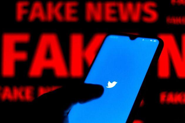 Logo de Twitter con un cartel de fondo que dice noticias falsas en