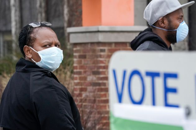 Voters masked against the coronavirus line up to vote at Riverside High School in