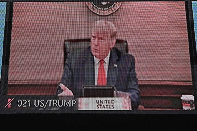 US President Donald Trump is pictured on a monitor screen as he takes part in the online Asia-Pacific...