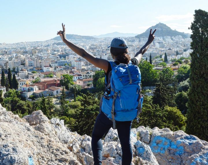 The author in 2017 overlooking Athens, Greece, during the three weeks I traveled carrying only my blue backpack.