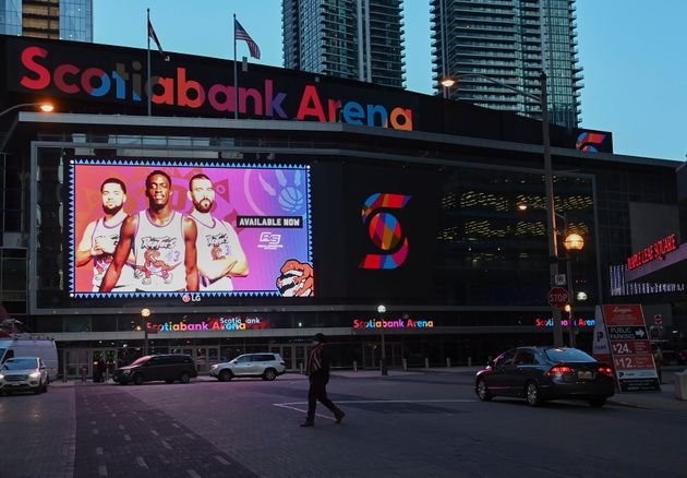 People walk past the Scotiabank Arena, where the Toronto Raptors and the Toronto Maple Leafs play, in...