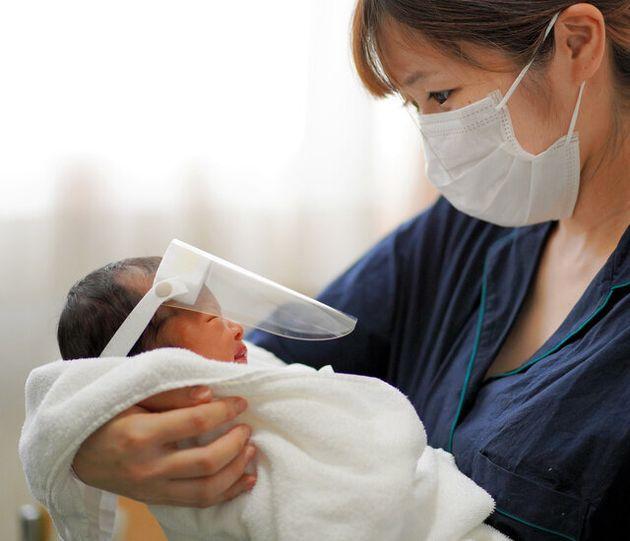 新生児用のフェースガードをつけた赤ちゃんを抱く母親(写真と本文は関係ありません)
