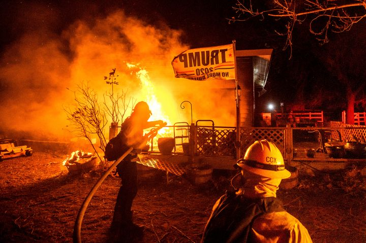 Firefighters spray water on a burning home as the Mountain View Fire tears through the Walker community in Mono County, Calif