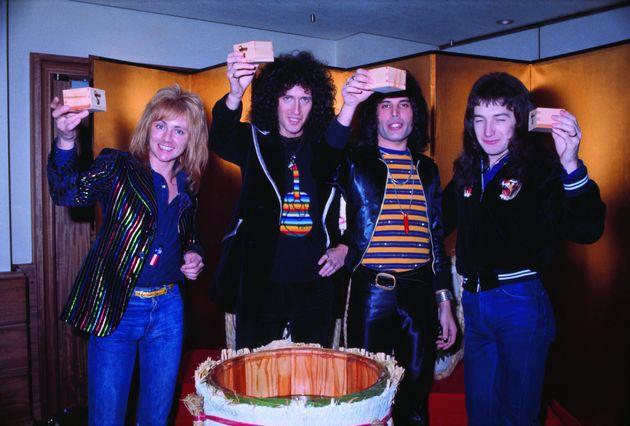1976年3月30日、ホテルパシフィック東京で。金屏風を背景に、樽酒を前にますを掲げるメンバーたち。左から、ロジャー・テイラー、ブライアン・メイ、フレディ・マーキュリー、ジョン・ディーコン