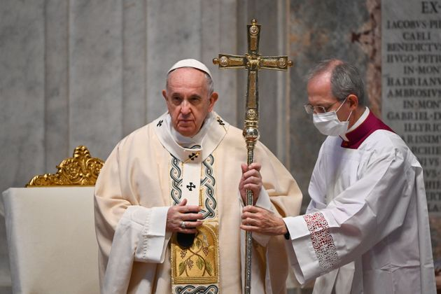 Pope Francis (L), assisted by Master of Pontifical Liturgical Ceremonies, Italian priest Guido Marini,...