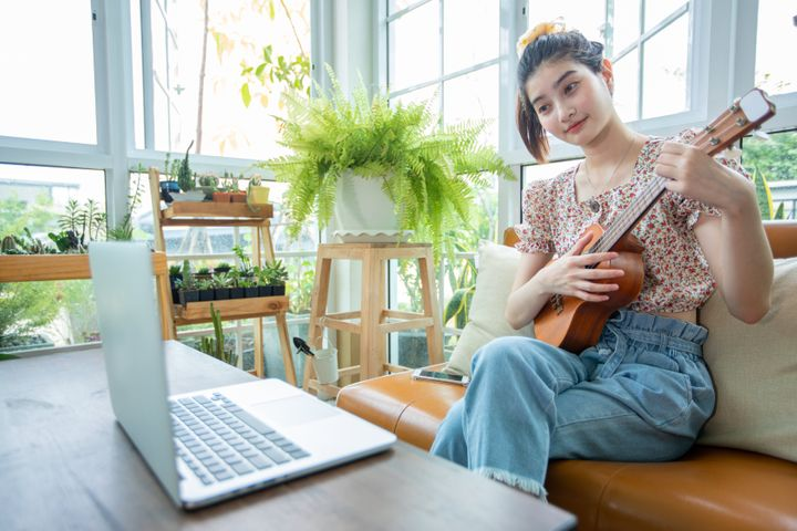 A woman learns a musical instrument online