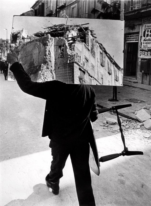 A man walks through the destroyed roads of Avellino, southern Italy, Nov. 28, 1980. He is carrying a...