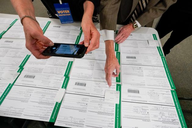 A canvas observer photographs Lehigh County provisional ballots, Friday, Nov. 6, 2020, in Allentown,...