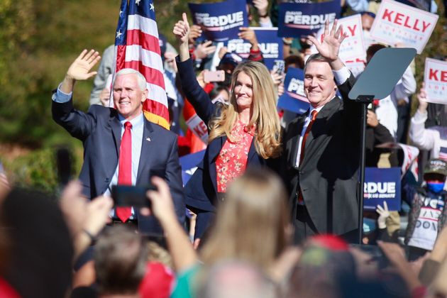 Vice President Mike Pence (from left) and Sens. Kelly Loeffler and David Perdue wave to supporters at...