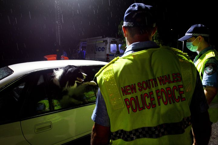 NSW police greet a dog in a vehicle stopped at the border checkpoint at South Albury as they prepare to reopen on November 23, 2020 in Albury, Australia. The New South Wales reopened its border to Victoria at 12:01 on Monday 23 November, with people able to freely travel into NSW for the first time since border restrictions were put in place in July due to Victoria's second wave COVID-19 outbreak. (Photo by Lisa Maree Williams/Getty Images)
