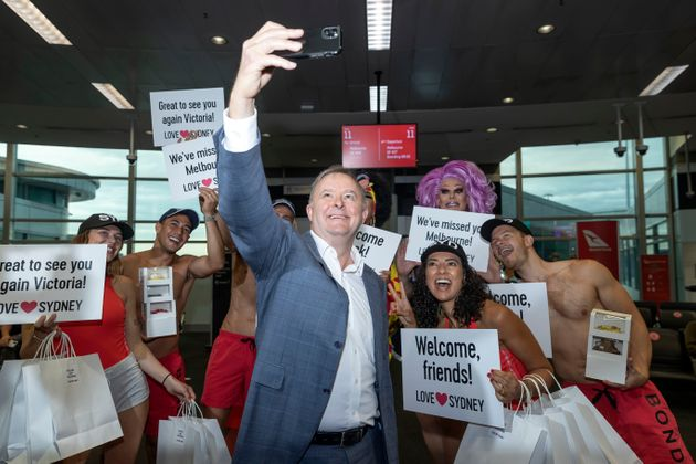 Labour leader Anthony Albanese poses for a photo with models waiting to greet passengers from Melbourne...