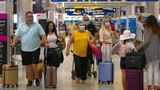 Travelers wearing protective face masks walking through Concourse D at the Miami International Airport on Sunday, Nov. 22, 2020, in Miami, Fla. With the coronavirus surging out of control, the nation's top public health agency pleaded with Americans not to travel for Thanksgiving and not to spend the holiday with people from outside their household. (David Santiago/Miami Herald via AP)