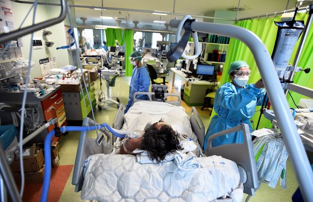 A patient suffering with the coronavirus disease (COVID-19) is treated in the intensive care unit of...