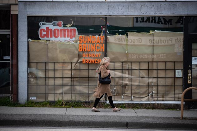 A woman walks past a restaurant in Vancouver closed due to COVID-19 on May 6, 2020. The new Canada Emergency...