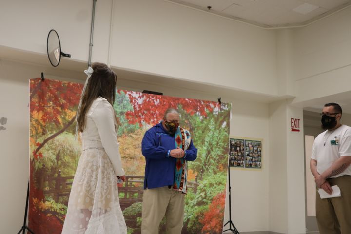 The author and her husband at their wedding in the prison visit room with their chaplain Brian Henry.
