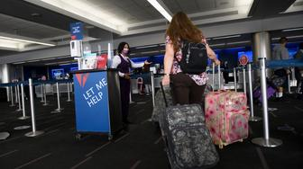 Passengers check bags for a Delta Air Lines, Inc. flight during the Covid-19 pandemic at Los Angeles International Airport (LAX) in Los Angeles, California, November 18, 2020. (Photo by Patrick FALLON / AFP) (Photo by PATRICK FALLON/AFP via Getty Images)