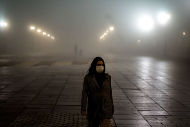 Una mujer pasea entre la niebla en