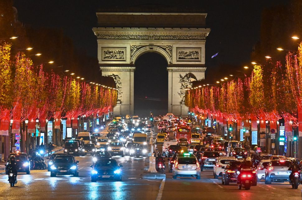 Christmas lights decorate the trees along the Champs-Elysees in Paris on Monday. Many European countries will this week unvei