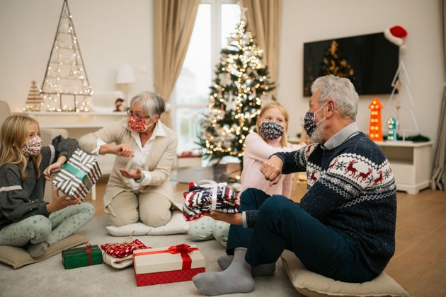 Two twin girls opening gifts with their grandparents at home for Christmas, wearing a protective face...