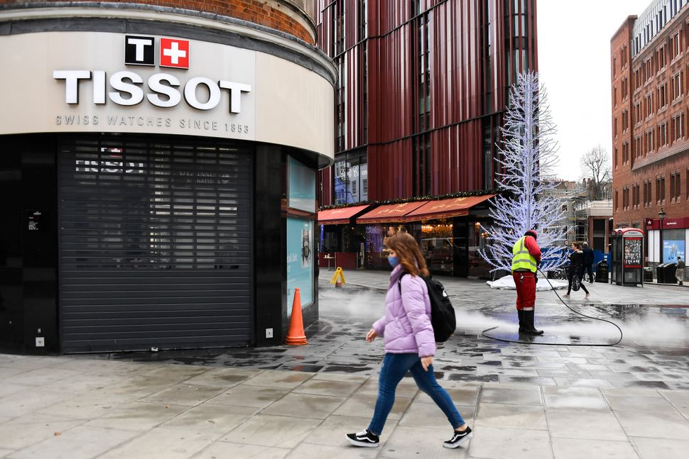 A woman walks past a closed shop while a man cleans the deserted pavement near Oxford Street in London on Tuesday. Oxford Str