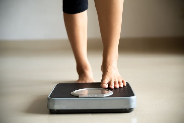 A woman steps onto a scale in this undated stock photo. Approximately one-third of Canadians surveyed in a new poll said they're exercising less during the coronavirus pandemic.