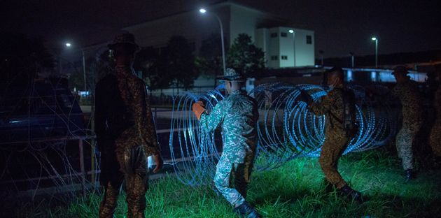 Military personnel install barbed wire around the Top Glove worker's hostel in Klang, Malaysia, on Nov.
