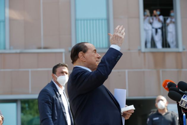 Italian former Premier Silvio Berlusconi waves as he leaves the San Raffaele hospital in Milan, Italy,...