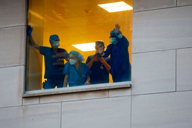 Health-care workers watch from behind a window at Toronto General Hospital as Toronto first responders...