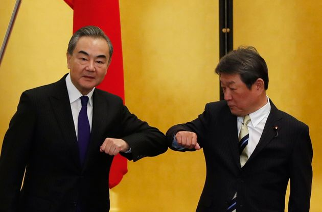 왕이 중국 외교부장이 모테기 도시미쓰 일본 외무상과의 회담에 앞서 악수 대신 '팔꿈치 인사'를 나누고 있다. 도쿄, 일본. 2020년