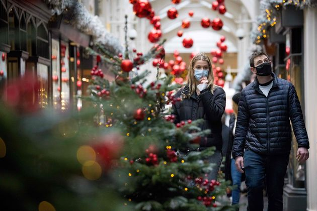 Pedestrians wearing face masks walk past Christmas-themed window displays inside Burlington Arcade in...