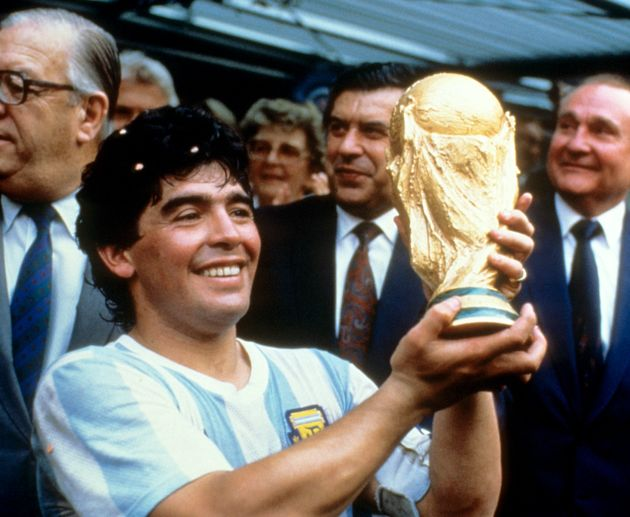 Diego Maradona holds up the World Cup trophy in