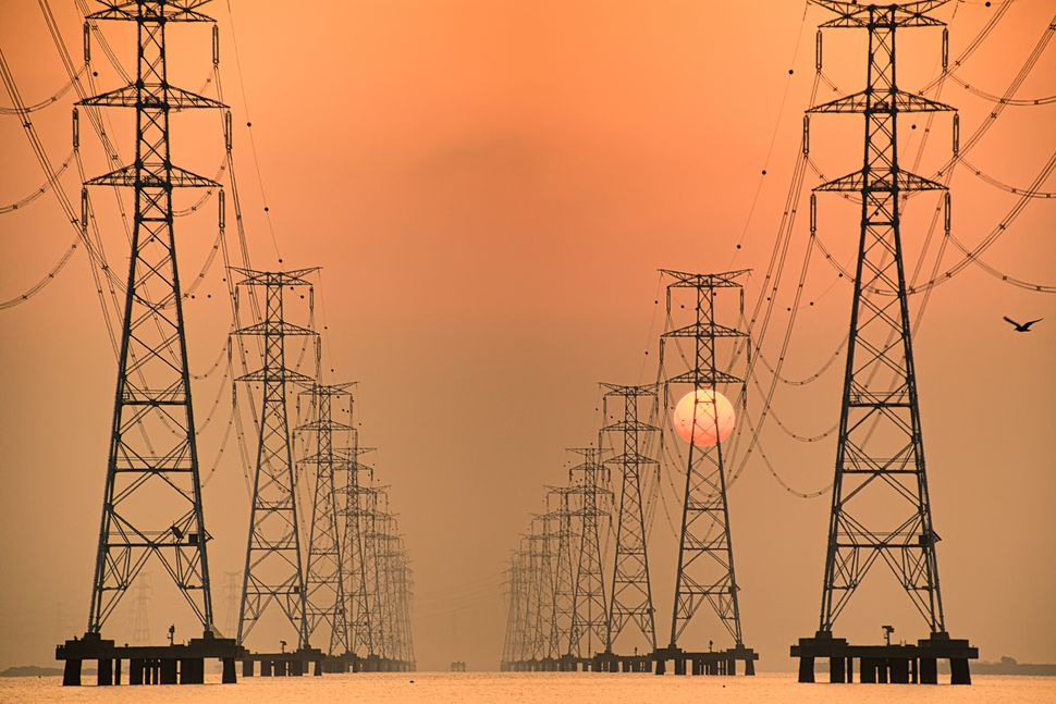 The sun rises behind Sihwa Lake Pylon VD702. The Sihwa Lake Tidal Power Station in South Korea is the...