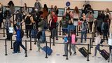 Air travelers line up to go through a security checkpoint at Salt Lake City International Airport Wednesday, Nov. 25, 2020, in Salt Lake City. (AP Photo/Rick Bowmer)
