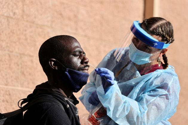 A man takes a coronavirus test at a Los Angeles Mission homeless shelter Thanksgiving meal giveaway,...