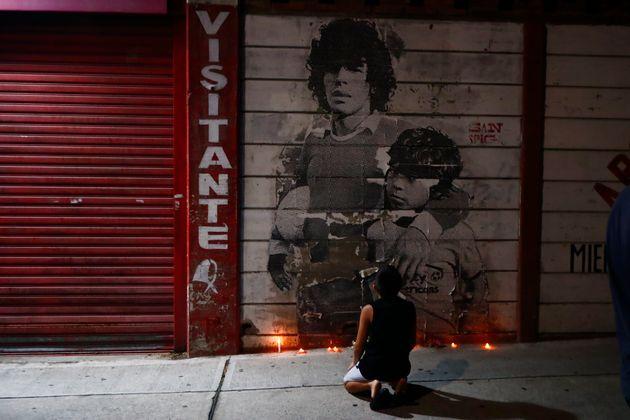Un chico se arrodilla ante un mural de Diego Maradona decorado con velas, en el estadio de Argentinos...