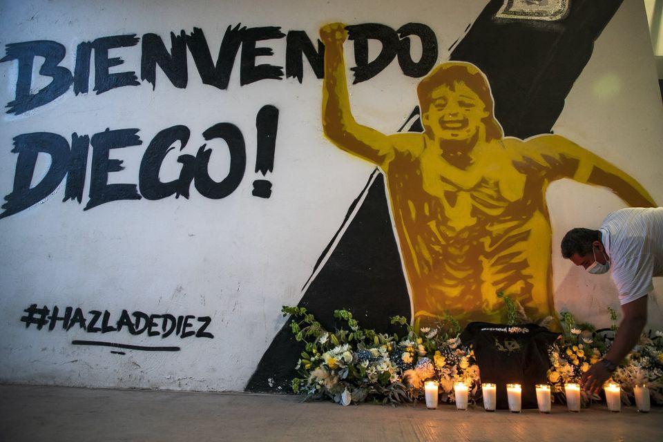 한 남성이 멕시코의 한 지역에 그려진 벽화 앞에서 디에고 마라도나를 추모하고