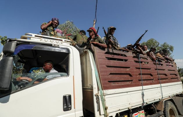 Members of Amhara region militias ride on their truck as they head to face the Tigray People's Liberation...